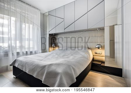 Modern bedroom in gray finishing and wooden floor