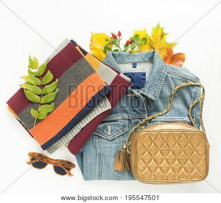 Autumn fashion woman autumn outfit on white background. Blue denim jacket retro sunglasses bronze crossbody bag stripe scarf. Flat lay top view