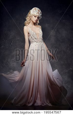 Tiara crown on head blonde girl. Woman in fairy dress mysterious magical fairy. Ethnic blond woman on gray background