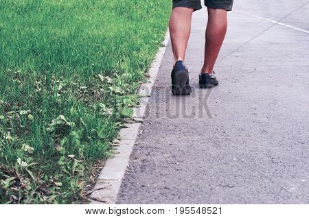 Legs of a young man leaving for the distance in the sartra.