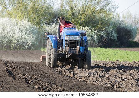 The farmer cultivates the garden with a tractor