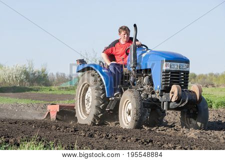 Man on blue tractor on blue sky background