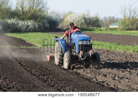 Farmer cultivates the land and looks down