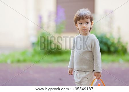 Little Beautiful Boy With Long Hair And Blue Eyes Holding A Bucket Of Toys For The Sandbox
