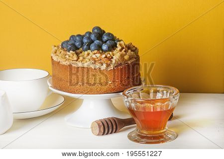 Homemade Cake With Nuts And Blueberries. A Cup Of Tea, Honey And