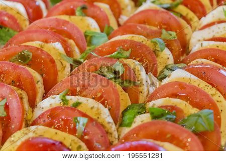 Delicious tomatoes and buffalo mozzarella chopped in salad row. Wonderful vegetarian vegan appetizer. Green bio and local food. Tomato and cheese in rows with herbs and basil. Healthy nutrition.