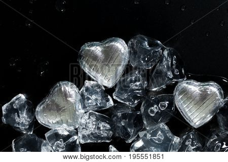 Melt my heart concept with silver wrapped chocolates and ice cubes all melting on a dark background