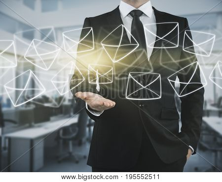 Businessman holding glowing digital letters in blurry office interior. E-mailing concept. 3D Rendering