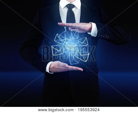 Businessman holding glowing digital letters on dark blue background. Email network concept