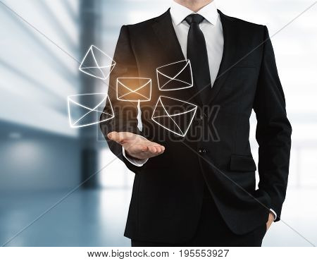 Businessman holding glowing digital letters in blurry interior. Email networking concept. 3D Rendering