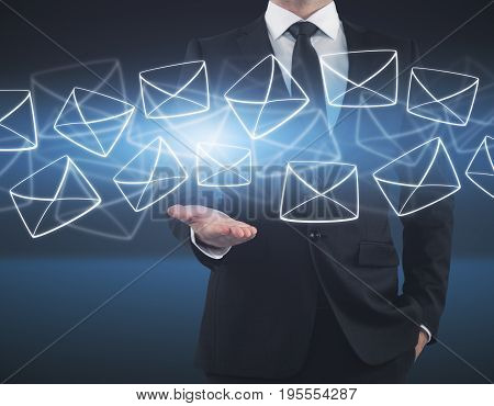 Businessman holding glowing digital letters on dark blue background. E-mail concept
