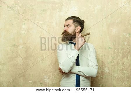 man or hipster with long beard and stylish hair on serious face in tie and white shirt on textured beige background smoking cigar copy space