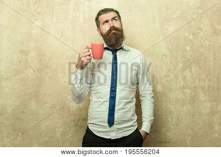 man. businessman with long beard and stylish hair on surprised face in tie and white shirt on textured beige background drink tea from coffee cup morning and energy refreshment