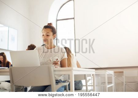 Young educator using laptop computer to run an online class on graphic design working in a crowded studio space. Education concept.