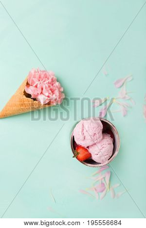 Ice cream in a waffle cone on a turquoise background. Strawberry ice cream. Flowers in a waffle cone. Pink carnations. Flowers on a wooden background. Copyspace. Flower photo concept