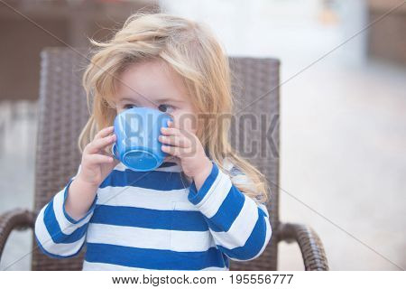 Boy drinking milk. Small child with blonde hair in striped blue and white shirt drinking milk from cup sitting in brown armchair