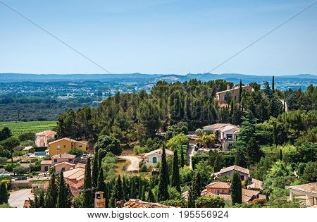 Panoramic of Provence hills seen from the village of Châteauneuf-du-Pape, with roofs, trees, blue sky and sunny day. In the Vaucluse department, Provence-Alpes-Côte d'Azur region, southeastern France