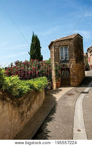 Street view with stone house in the center of the village of Châteauneuf-du-Pape, blue sky and sunny day. Located in the Vaucluse department, Provence-Alpes-Côte d'Azur region in southeastern France