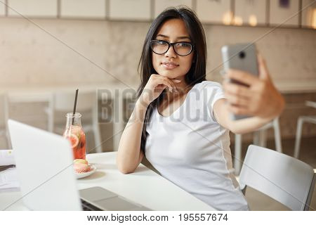 Women like themselves. Young asian student making a selfie at cafe using a mobile phone looking pretty awesome.