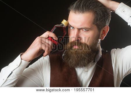 Man Holding Bottle Of Red Liqueur At Frown Face