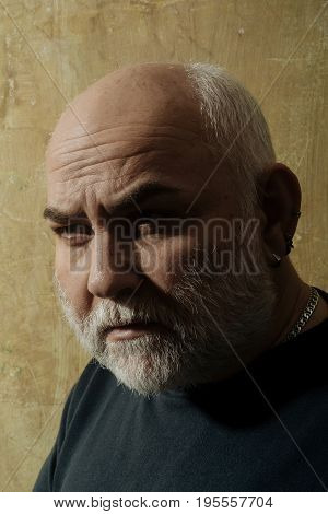 Man with grey beard and moustache on old face with wrinkled skin and bald head. Grandfather or senior person in black sweater on beige wall. Hair loss. Time age and aging