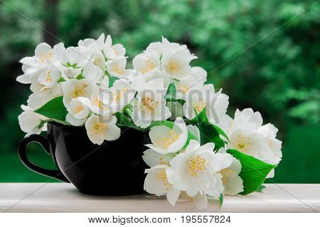 White jasmine flowers in a black cup