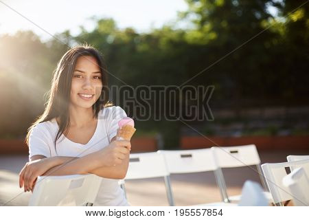Young woman eating ice cream in park during summer education break looking at camera smiling