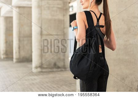 Glad slim girl is relaxing after training. She is standing outdoors and smiling. Focus on sporty backpack on her back. Copy space