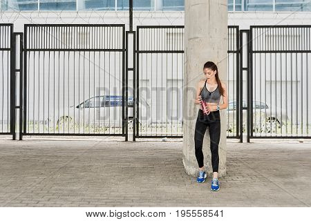Full length of pensive thirsty girl opening battle of water after training. She is standing outdoors and leaning on the column. Copy space in left side