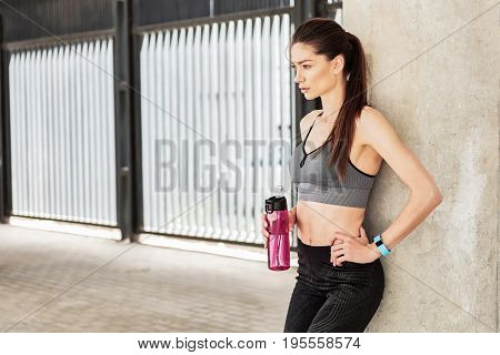 Portrait of confident fit woman resting after workout. She is holding bottle of refreshing beverage and leaning on column with relaxation. Copy space in left side