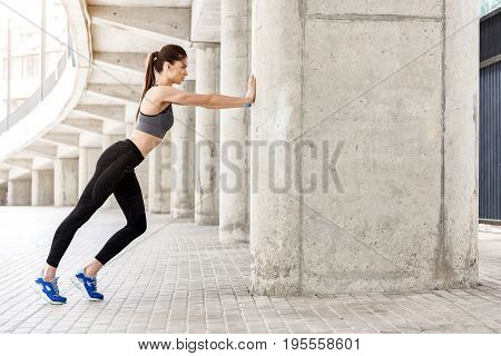 Aspirated young woman is warming up her body before training. She is standing and leaning on column by both arms. Copy space in right side