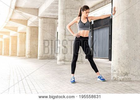 Pensive slim girl is posing while stretching arm to column in stadium. She is standing with arm akimbo while warming up before workout. Copy space in left side