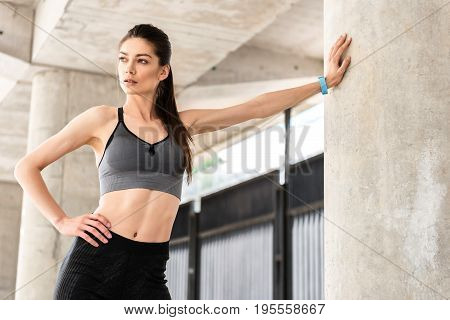 Strong sporty girl is making break after training outdoors. She is leaning on column by arm while standing with arm akimbo. Athlete is looking aside with aspiration. Portrait