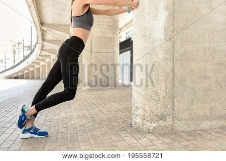 Low angle close-up of fit body of sporty girl doing warm-up before training. She is stretching arms and leaning it on column while standing in stadium. Copy space