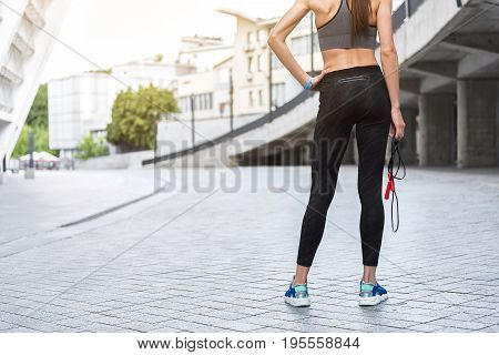 Close up of sporty body from the back of woman holding skipping rope. She is standing with arm akimbo near stadium. Copy space in left side