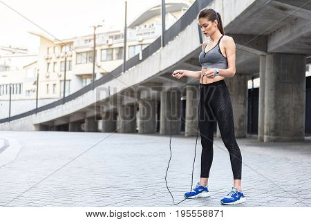 Conscious fit girl is ready for exercise with jumping-rope. She is standing outdoor and looking at equipment with seriousness. Copy space in right side