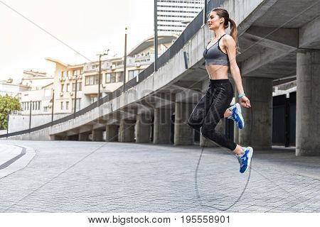 Happy young woman is jumping on a rope with enjoyment outdoors. She is laughing. Copy space in left side