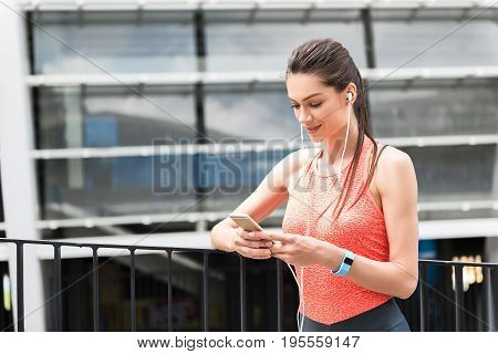 Waist up portrait of happy young woman resting after training. She is listening to music from earphones and looking at smartphone. Athlete is standing outdoors and smiling