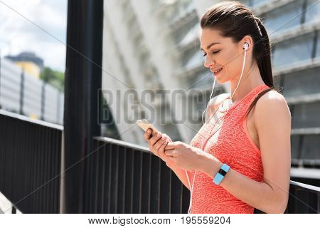 Side view profile of excited sportswoman listening to music while relaxing after workout. She is looking at cellphone and smiling. Copy space
