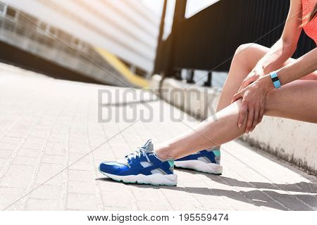 Close up of leg of young woman touching knee while feeling pain after running. She is sitting near road. Copy space in left side