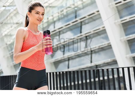 Portrait of happy girl resting after jogging. She is holding bottle of drink and smiling while looking forward with aspiration. Copy space in right side