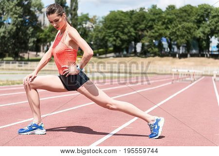 Confident young woman is warming up before running on track. She is kneeling and stretching leg behind with arm akimbo. Copy space in right side