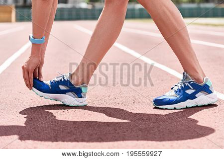Close up of female hands reaching down to her foot while standing on running track. Woman wearing sneakers during warm-up. Tracker on her hand