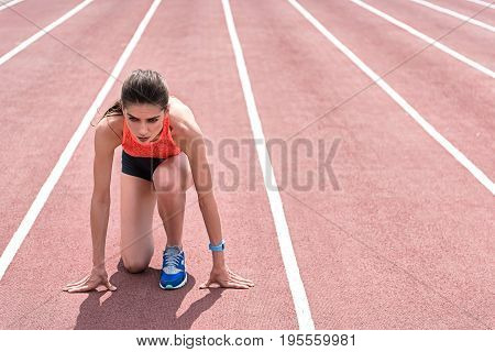 Nervous female runner is standing at starting position on track. She is looking forward with hope. Copy space