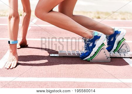 Close up of legs of young woman ready to leave the starting blocks on stadium. She is leaning arms on track
