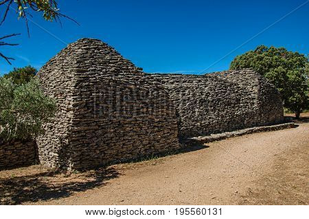 Path and huts made of stone under sunny blue sky, in the Village of Bories, near the town of Gordes. Located in the Vaucluse department, Provence region, in southeastern France