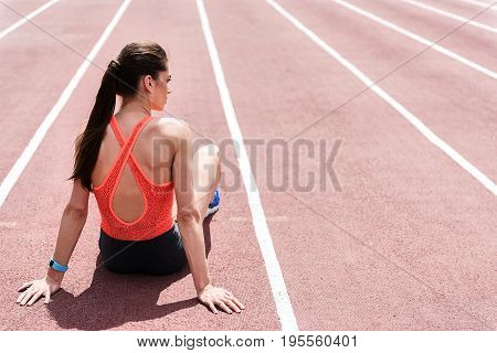 Pensive young woman is having rest after exercising in stadium. She is sitting on running track and looking aside thoughtfully. Focus on her back. Copy space