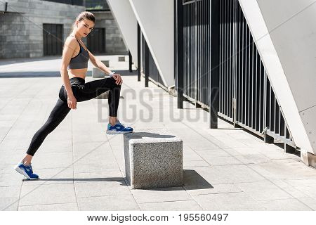 Full length portrait of self-assured young woman doing exercise outdoor. She is standing and looking at camera with confidence. Copy space