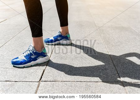 Close up of female sporty legs standing on road outdoor. Focus on her sneakers and shadow