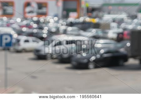 Abstract blurred parking next to modern shopping mall at peak hour. For background , backdrop, place for your text